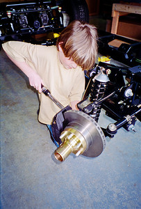 This archive photo provides a good view of the front suspension arms. My youngest son Bryce checks the torque on the front caliper bolts. This was probably early 1997. Note the beautiful pin-drive hubs and brake disc.