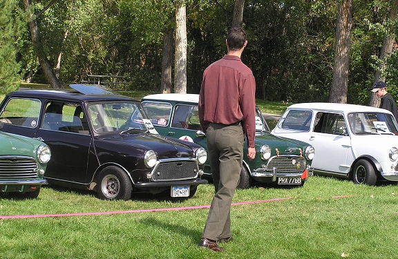A tall man walking near the classics.