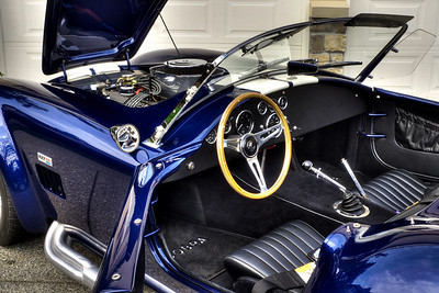 Uncluttered dash features original style English Smiths gauges, with 'correct reverse 180 mph speedometer. Lucas toggle switches. Period-correct Ford toploader 4-speed gear shifter and knob. Hurst Competition Plus shift linkage.