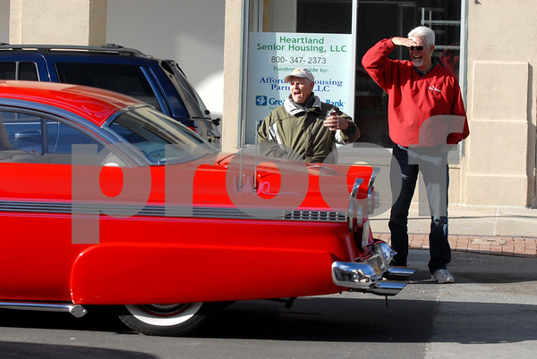 -Messenger photo by Hans Madsen<br /> <br /> Paul Halverson, left, and his cousin, Greg Halverson, both of Fort Dodge, cheer on the passing cars Saturday afternoon during the Cruise to the Woods car show Shag the Drag event on Central Avenue in downtown Fort Dodge. The pair said they were both eager participants in the cruising tradition during their youth in Fort Dodge.