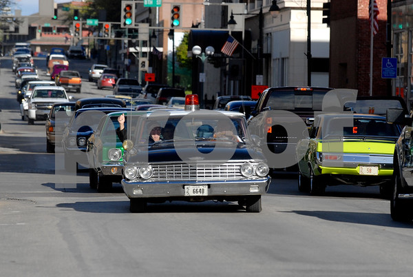 -Messenger photo by Hans Madsen<br /> <br /> Larry Sadler, at left, and Joe Chamberlain, of Eagle Grove, try to keep law and order in their 1962 Ford Galaxie painted to look exactly like the Mayberrry police car from the Andy Griffith Show. They carry fake tickets that may, or may not, have been issued to other participants in the Cruise to the Woods car show Shag the Drag event on Central Avenue in downtown Fort Dodge.