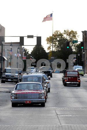 -Messenger photo by Hans Madsen<br /> <br /> Participants in the Cruise to the Woods car show Shag the Drag event drive down Central Avenue Saturday afternoon. Yes, that's a real Webster County Sheriff's vehicle joining the action at left.