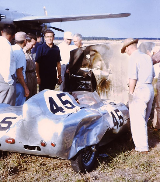 "Briggs Cunningham (blue shirt), and several race fans, looking over the burned-out engine compartment of Lotus Mk. XI he was to take possession of after the race. Colin Chapman is on his immediate right. (Gene Bussian/PCA photo) Source: <a href=""http://www.sportscardigest.com/1956-sebring-12-hours-grand-prix-race-profile/5/"">http://www.sportscardigest.com/1956-sebring-12-hours-grand-prix-race-profile/5/</a>."