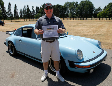 Rick Riley, holding the Best 1970s Porsche Award, smiles with his original Gulf Blue 1975 Porsche Carrera during the inaugural DeutscheMarques German auto event at the Gilmore Car Museum on July 7. Riley is a member of the West Michigan Region of the PCA. The event was sponsored by Zeigler BMW, Hayes Mercedes-Benz and Delta Porsche. (Bradley S. Pines / BSPines@gmail.com)