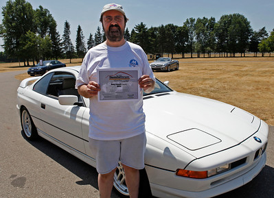 "Gary Apps of Kalamazoo, holding Best Classic BMW Award, smiles with his 1991 BMW 850ci V12 coupe during the inaugural DeutscheMarques German auto event at the Gilmore Car Museum on July 7. Apps, a longtime Michiana BMW CCA member and a DeutscheMarques organizer, said his car sports Brembo brakes, stainless brake lines, a sport suspension and a ""dorky"" rear spoiler. The event was sponsored by Zeigler BMW, Hayes Mercedes-Benz and Delta Porsche. (Bradley S. Pines / BSPines@gmail.com)"