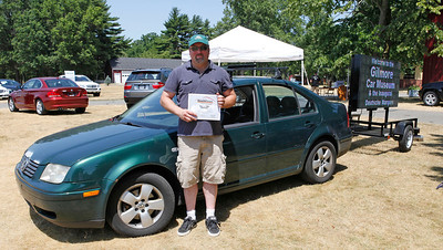 Holding the Best of the 1990s Volkswagen Award, Harold Walters with his 1999 Volkswagen Jetta TDI with 328K miles and an electronic sign during the inaugural DeutscheMarques German auto event at the Gilmore Car Museum on July 7. The event was sponsored by Zeigler BMW, Hayes Mercedes-Benz and Delta Porsche. (Bradley S. Pines / BSPines@gmail.com)