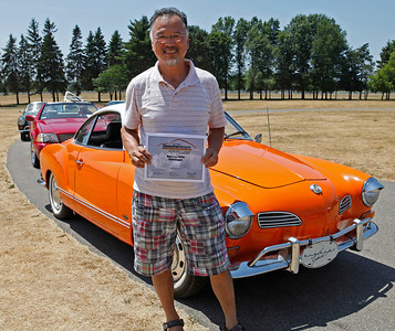 "Aki Tsuji of Delton, holding Best Porsche of the 1970s Volkswagen Award, smiles with his 1970 Karmann Ghia autostick coupe, a ""retirement toy"" during the inaugural DeutscheMarques German auto event at the Gilmore Car Museum on July 7. Tsuji is a member of The Good Volks. The event was sponsored by Zeigler BMW, Hayes Mercedes-Benz and Delta Porsche. (Bradley S. Pines / BSPines@gmail.com)"