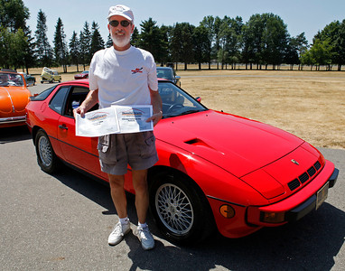 Paul Swope, holding Best Porsche of the 1990s and Cleanest Concours Porsche awards, smiles with the 1981 Porsche 924 Turbo he and his wife, Diana have owned since new during the inaugural DeutscheMarques German auto event at the Gilmore Car Museum on July 7. The Swopes are members of the PCA and the MBCA. The event was sponsored by Zeigler BMW, Hayes Mercedes-Benz and Delta Porsche. (Bradley S. Pines / BSPines@gmail.com)