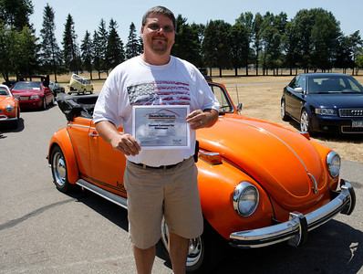 Jim Hanson of Battle Creek, holding the Cleanest Concours Volkswagen award, smiles with his 1972 Volkswagen Super Beetle convertible during the inaugural DeutscheMarques German auto event at the Gilmore Car Museum on July 7.  The event was sponsored by Zeigler BMW, Hayes Mercedes-Benz and Delta Porsche. (Bradley S. Pines / BSPines@gmail.com)