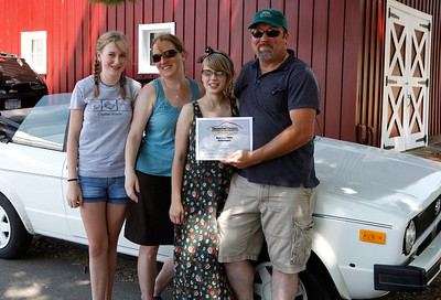 Holding their Best of the 1980s Volkswagen Award, Harold Walters and his family smile with their 1986 Volkswagen Cabriolet during the inaugural DeutscheMarques German auto event at the Gilmore Car Museum on July 7. The event was sponsored by Zeigler BMW, Hayes Mercedes-Benz and Delta Porsche. (Bradley S. Pines / BSPines@gmail.com)