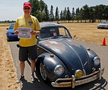 Bran Hartman of Battle Creek smiles with his award-winning classic 1967 Volkswagen beetle during the inaugural DeutscheMarques German auto event at the Gilmore Car Museum on July 7.  The event was sponsored by Zeigler BMW, Hayes Mercedes-Benz and Delta Porsche. (Bradley S. Pines / BSPines@gmail.com)