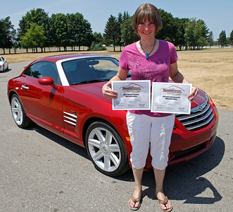 Emily Michaelis of Niles, holds the Best Special Feature and Cleanes Concours Awards her 2005 Blaze Red Crystal Chrysler (M-B) Crossfire won during the inaugural DeutscheMarques German auto event at the Gilmore Car Museum on July 7. The car, assigned her lucky number 29, has been hers since 2006. The event was sponsored by Zeigler BMW, Hayes Mercedes-Benz and Delta Porsche. (Bradley S. Pines / BSPines@gmail.com)