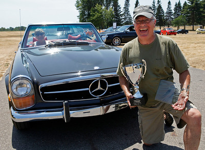 Jon Smucker of Goshen, Indiana smiles in front of the 1970 Mercedes-Benz 280SL that he owns with wife, Jan, in the passenger seat. Their car was judged Best in Show Mercedes-Benz during the inaugural DeutscheMarques German auto event at the Gilmore Car Museum on July 7. Smuckers'  names will be the first engraved on the annual Hayes Mercedes-Benz Cup, which will be on display at the Kalamazoo dealership, the exclusive Mercedes-Benz sponsor of DeutscheMarques.  (Bradley S. Pines / DeutscheMarquesAG.com)