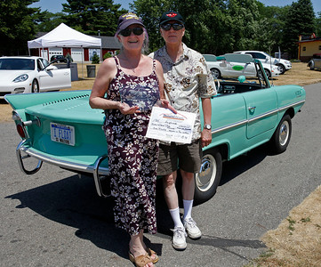 """Gloria and James Tiller of Kalamazoo smile at the stern of their 1966 Amphicar 770. The plate says it all """"I FLOAT."""" Their car/boat was judged Best in Show in the Other German Marque during the inaugural DeutscheMarques German auto event at the Gilmore Car Museum on July 7. The Tillers own and operate Kzoo Books, a pair of independent new and used bookshops in Kalamazoo. (Bradley S. Pines / DeutscheMarquesAG.com)"""