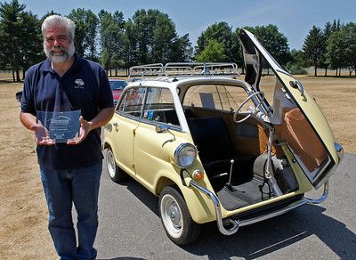 Hector Orlandi of Kalamazoo smiles in front of his 1958 BMW 600 which was judged Best in Show BMW during the inaugural DeutscheMarques German auto event at the Gilmore Car Museum on July 7. Orlandi's name will be the first engraved on The Harold Zeigler BMW Cup (not pictured) which will be on display at the Kalamazoo dealership, the exclusive BMW sponsor of DeutscheMarques.  (Bradley S. Pines / DeutscheMarquesAG.com)