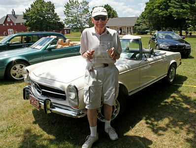 Frederic Nugent of Holland, Michigan, holds his Best in Show trophy in front of his 1969 Mercedes-Benz 280SL with an unusual ivory over green color combination. His prized convertible boasts 109,000 miles on the odometer.
