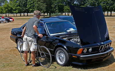 A cyclist peeks at a BMW M6 on display during the inaugural DeutscheMarques German auto event at the Gilmore Car Museum on July 7. Many Michiana Chapter BMW CCA members attended. Event sponsors Zeigler BMW, Hayes Mercedes-Benz and Delta Porsche displayed a variety of new cars.  (Bradley S. Pines / BSPines@gmail.com)