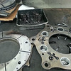 Disassembled pressure plate, with some clutch discs in the back.