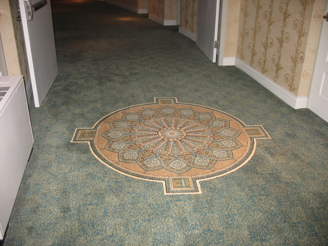 A compass in the carpet in the hall way outside the door to our room.