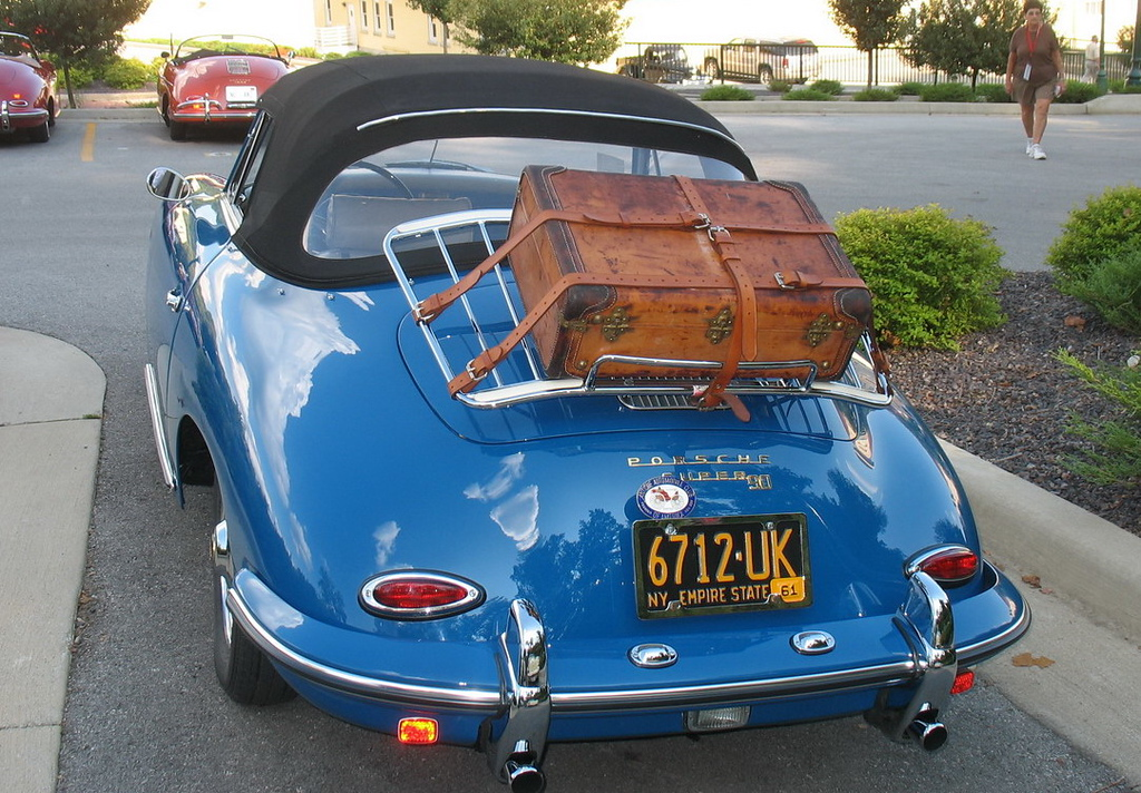 A car with Porsche luggage on the luggage rack.