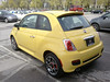 Fiat 500 nudging the corral gate, sniffs the winds of freedom, while the guys in the dealership take care of paperwork.