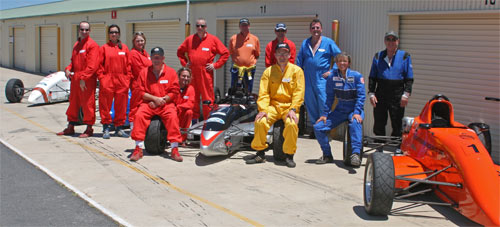 Liam Honor, Felicity Benn, Kerrin Barnes, Paul Patten, Marcus Patten (behind),Neville West-Lewis, Herman Heiligers, Steven Kouparitsas, Len Greenhalgh (sitting), David Mitchell, Elke Patten, John Jacobs (Con Lolis not present) with the cars at the Wakefield Park day for AAPT (Canberra).