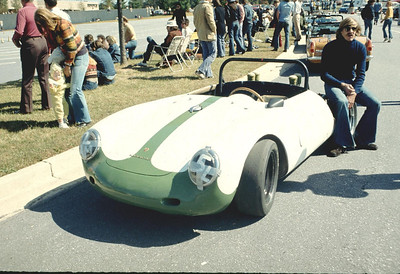 Jim Finan resting on the rear wheel of Ernie's Porsche 550A Spyder at an autocross.