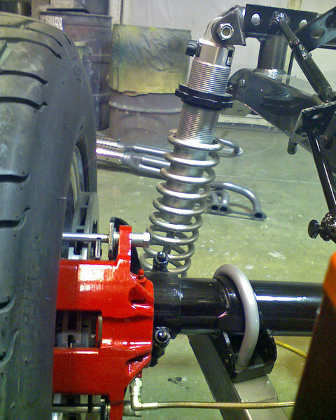 Rear suspension and brake assembly. ..Exhaust pipes on the floor.