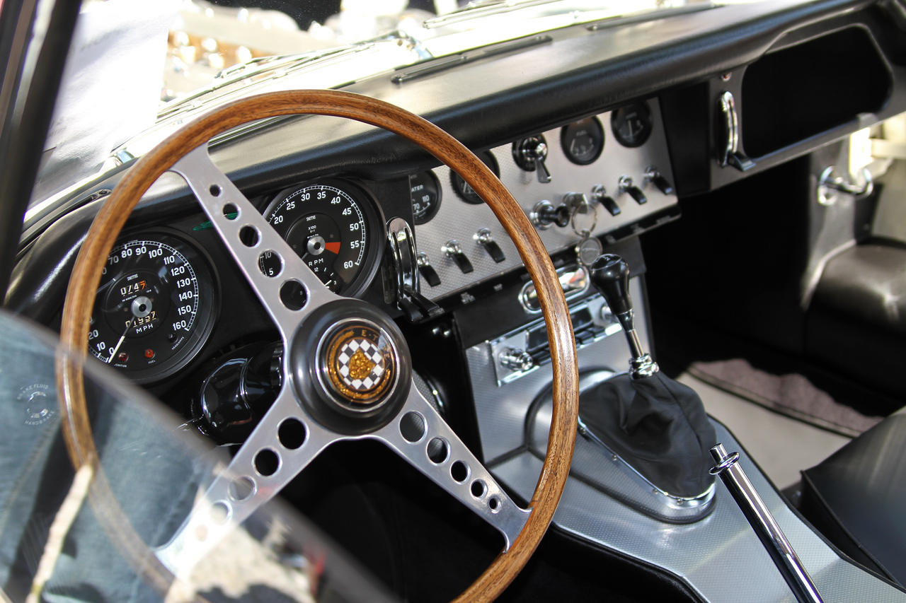 Interior with lots of very nice brushed aluminum panels and a classic wood steering wheel.