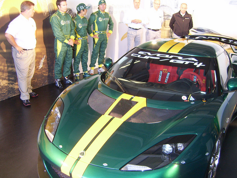 FAST TRACKER -- The racing version of the new Evora sports car by Lotus. Jimmy Vasser is the third driver in the Lotus driver's suit from left.