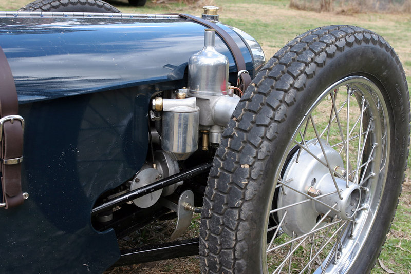 """Austin Seven engine with twin Roots-type superchargers, 40 psi, one x 2 3/16"""" SU, Methanol. Steel crank, extra head bolts through to crankcase, hydraulic brakes but still those delightful spindly wheels and hubs. Radiator below the height of the 19"""" tyres... that's low.<br /> <br /> Ulster bent front axle."""
