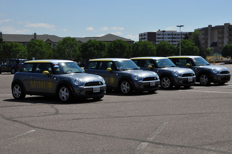 """MTTS Day 3. Four electric, experimental MINI """"E"""" vehicles await the transport back home (extension cord too short for this trip)."""
