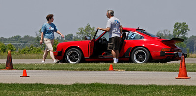 Eve Dolenski, left, chats with Matt Napieralski who drove his Porsche 911 to 2nd in Class E and 5th overall with a best time of 45.834.  A record 32 drivers competed in the opening round of the Michiana BMW CCA autocross season at the Tire Rack on May 19, 2012. (Bradley S. Pines / CONTACT: OneTrackMind.brad@gmail.com)