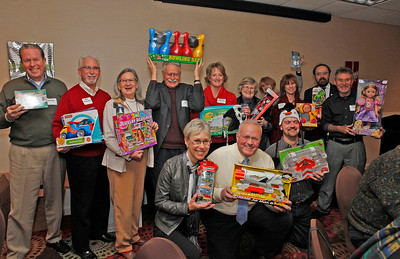 Members hold up some of the gifts donated to the United States Marine Corps Reserve program Toys for Tots.