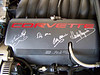 Autographed fuel rail cover (left to right) Dennis Gage (My Classic Car), race car driving great Stirling Moss, Bobby Allison, Hurley Haywood.