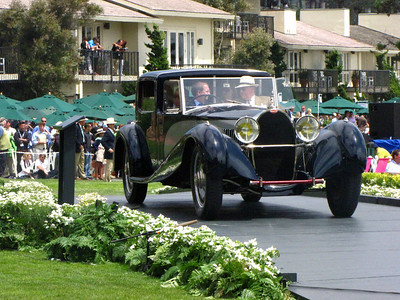 (a) Master of Ceremonies Edward Hermann arrives in a Bugatti Type 41 Royale Coupe de Ville Binder