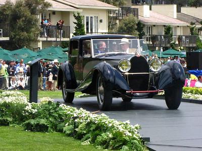 (a) Master of Ceremonies Edward Hermann arrives in a Bugatti Type 41 Royale Coupe de Ville Binder