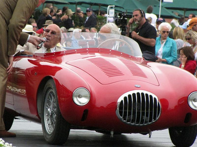 (e) The Concours honored Sir Stirling Moss. Here is shown in an OSCA MT4 that he once raced.