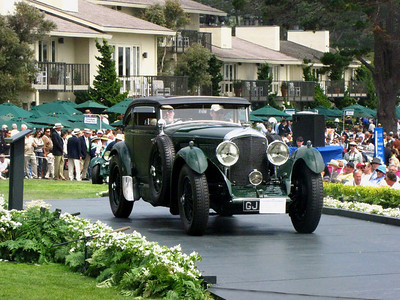 (b) Concours Chairwoman Sandra Button is driven to the platform in the Bentley Speed Six Gurney Nutting Coupe