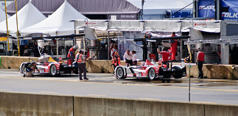 View from the support paddock side of the start finish pedestrian  bridge, looking across the track at the main pit lane. The two Audi R15+'s sit in their pit boxes prior to the start of Thursday morning ALMS practice.
