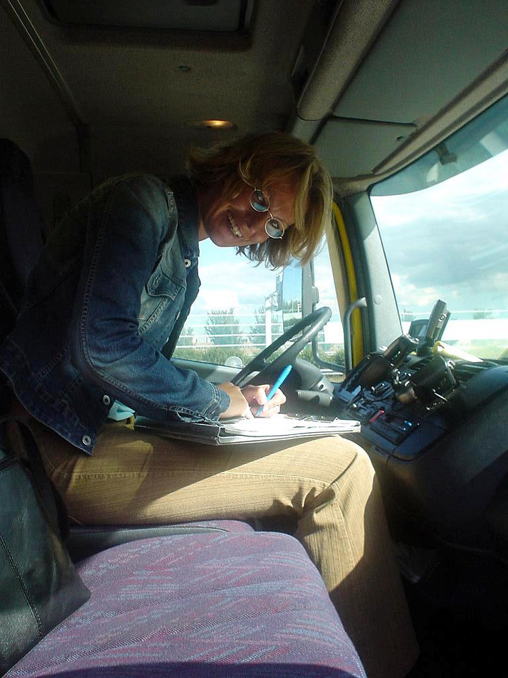 Petra filling out insurance papers in the tow truck