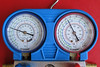 Gauge indications with the engine idling after an additional filling with R134a.<br /> <br /> The low (blue) pressure indication is at 27 psi and the high (red) pressure indication is at 205 psi.<br /> <br /> Increasing the engine RPM would decrease the low pressure indication and increase the high pressure indication, which is normal.<br /> <br /> According to the Porsche manual, at 25º C, high pressure indication should be 150 to 215 psi and the low pressure indication should be 8 to 16 psi.<br /> <br /> The A/C system was blowing ice cold when the condensor fan was at high speed.