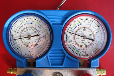 Gauge indications with the engine idling after a partial fill with R134a.  The low (blue) pressure indication is at 15 psi and the high (red) pressure indication is at 145 psi.  Increasing the engine RPM would decrease the low pressure indication and increase the high pressure indication, which is normal, but to levels lower than specified by the Porsche manual at an ambient temperature of 25º C.  At 25º C, high pressure indication should be 150 to 215 psi and the low pressure indication should be 8 to 16 psi.  Further topping up with R134a was needed.