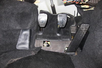 The pedal assembly with the driver's side carpet removed.  There is a plastic cap holding the carpet down at the rear of the carpet that must be removed first.  The accelerator pedal has been released from the ball end of the accelerator rod. This is done by pulling the accelerator pedal towards the rear of the vehicle.