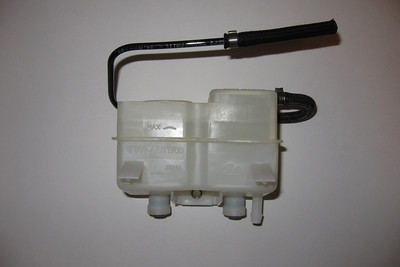 The side of the hydraulic fluid reservoir adjacent to the body.  The rubber overflow / vent hose can be removed more easily from the plastic pipe it is attached to when heated by a heat gun.  The reservoir was thoroughly washed and rinsed before being flushed with 70% alcohol to remove the water.