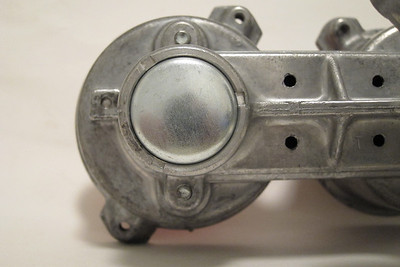 """As recommended by various do-it-yourself web sites to use the following method, I chose not to use a small screwdriver to remove the end cap by prying at the edges of the distributor housing. I didn't want to mark/gouge the distributor housing.  Instead, the original end cap was removed by drilling a small hole through it and then using a hooked pick to then pry it out. The metal of the original end cap is quite soft and thin.  As a replacement for the original end cap, a 1 1/4"""" frost plug was used. One with a 1/4"""" wall height fit perfectly. Not bad for under $2.  The inside edges of the distributor body where the stake marks are located were filed down smooth using a small jeweler's file. This made tapping in of the frost plug possible.  Also, so that the edge of the frost plug does not scrape the distributor body thereby possibly introducing aluminum shavings in the bearing area, the edge was filed at a shallow angle with a fine flat file."""