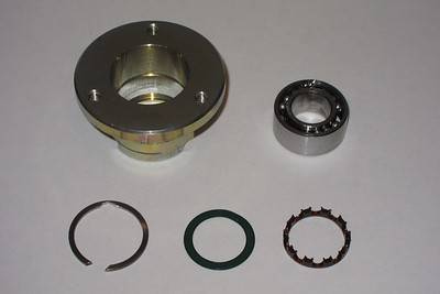 The components of the fan hub bearing.  From top left, clockwise... The fan hub, the dual row 17 x 32 x 14 ball bearing, one of the two bearing cages used to separate the ball bearings (one inserted into each side), one of the two bearing seals (one inserted into each side) and the snap-ring that retains the bearing in place.  The snap-ring is next to impossible to remove due to the design. One end is angled such that it cannot be used to extract the snap-ring, and the other end, although angled correctly, is no better.  A small grinding stone on a Dremel was used to weaken the end opposite the open end of the snap-ring in order to weaken it so that it could be collapsed enough to extract it.
