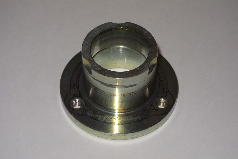The side of the the fan hub adjacent to the cooling fan.<br /> <br /> The three threaded holes are M6 x 1.00.<br /> <br /> The fan hub bearing has been removed. Part way down the bore is the groove for the snap-ring that holds the bearing in place. The bore above the snap-ring groove is where the bearing is mounted. The bore below the snap-ring groove is slightly larger in diameter so that the bearing drops out when it is pressed out beyond that point.