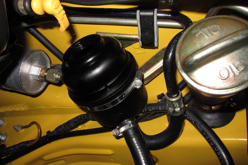 Prior to adding any fluid, the inside of the power steering reservoir was cleaned. An insignificant amount of soot was found on the base plate.<br /> <br /> Normally I would remove the power steering reservoir for a thorough cleaning, but it could only be removed by cutting the Oetiker Stepless Ear Clamp on the return hose (not visible - behind the hose to the power steering pump). The hose to the power steering pump has a screw clamp as can be seen.<br /> <br /> Fill the power steering fluid reservoir to within an inch of the top with Pentosin CHF 202.<br /> <br /> Reinstall the DME relay and start the engine for 5 seconds while rotating the steering wheel back and forth. Refill the power steering reservoir and repeat this step, this time letting the engine run while turning the steering wheel fully to each end a few times.<br /> <br /> Check the power steering fluid level in the reservoir and top up as necessary.<br /> <br /> If at any time the power steering pump is sucking air, shut the engine off and add power steering fluid.<br /> <br /> Check for leaks at the hydraulic fittings at the steering rack.<br /> <br /> Reinstall the underbelly cover and reconfirm the level of the power steering fluid.