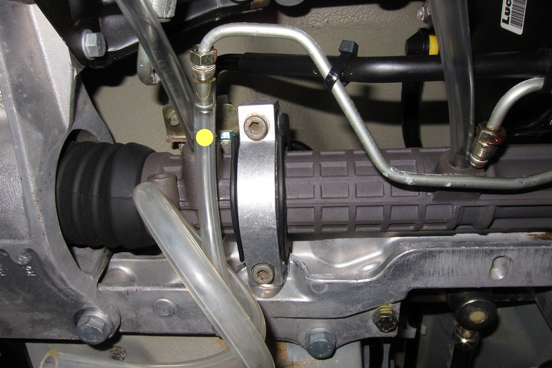 Slip a snug fitting vinyl hose over the end of each hydraulic line (only one hose shown in this photo) and place the other ends in a container.<br /> <br /> Remove the DME relay and using the ignition key, crank the engine over for a few seconds while rotating the steering wheel back and forth. Observe the previously clear vinyl hoses to verify if any additional old power steering fluid has drained.<br /> <br /> Fill the power steering fluid reservoir with fresh power steering fluid (Pentosin CHF 202). Crank the engine over again for a few seconds while moving the steering wheel back and forth. Verify if fresh power steering fluid has been pumped through the drain lines (Pentosin CHF 202 should be green in color).<br /> <br /> When the fresh power steering fluid has ceased to drain, remove the four vinyl hoses previously installed.<br /> <br /> Carefully reinstall the O-rings on the hydraulic lines. Apply a thin smear of Dow Corning MolyKote 55 O-ring lubricant to the O-rings.<br /> <br /> Carefully insert the hydraulic lines back into the steering rack keeping them square and thread the fittings back on. Do not over tighten the fittings; the O-rings create the seal.<br /> <br /> Wipe the area around the fittings with damp cloth soaked in alcohol. They should appear dry so that you can check for leaks.